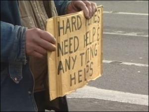 "panhandler and sign that reads ""Hard times, need help, anything helps."""